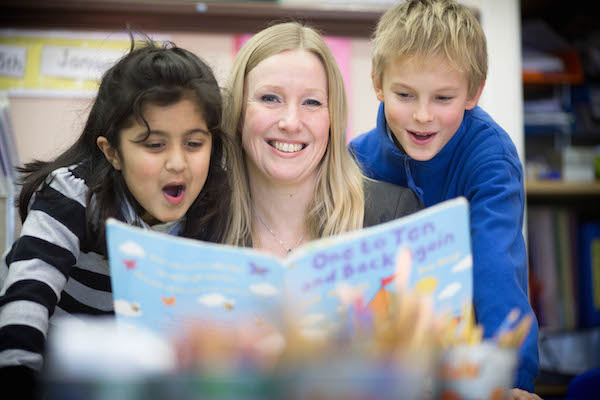 Picture of teacher and two primary-aged pupils looking at a book