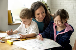 Picture of mother sitting with two children drawing and playing on ipad