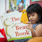 Picture of young child reading a book