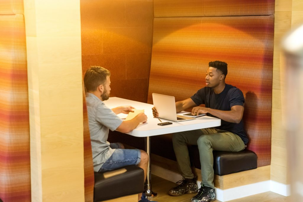Picture of two men sitting at a table with a laptop