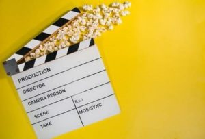 Picture of a film clapperboard with popcorn